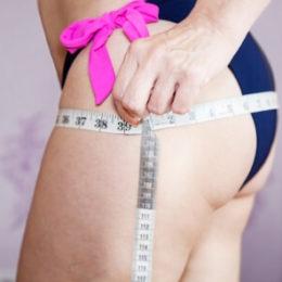Женщина измеряет объем бедер